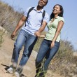 Couple walking on path holding hands and smiling — Foto Stock