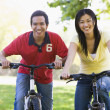 Couple on bikes outdoors smiling — Stock Photo