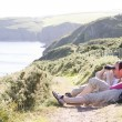 Couple on cliffside outdoors using binoculars and smiling - Stock Photo
