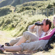 Couple on cliffside outdoors using binoculars and smiling — Stock Photo