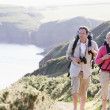 Couple on cliffside outdoors walking and smiling - Stok fotoraf