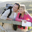 Couple on cliffside outdoors leaning on railing and smiling — Stock Photo