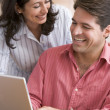 Couple in kitchen using laptop smiling — Stock Photo