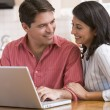 Couple in kitchen using laptop and smiling — Stock Photo