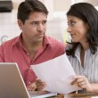 Foto Stock: Couple in kitchen with paperwork using laptop looking unhappy