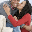 Couple in living room kissing and smiling — Stock Photo