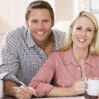 Couple in kitchen with newspaper and coffee smiling - Photo