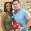 Couple in bowling alley holding ball and smiling — Stock Photo