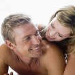 Couple lying in bed smiling — Stock Photo #4767915