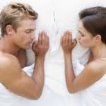 Couple lying in bed sleeping — Stock Photo