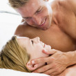 Couple lying in bed smiling — Stock Photo #4767932