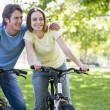Couple on bikes outdoors smiling - ストック写真