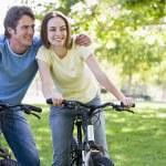 Couple on bikes outdoors smiling — Stock Photo #4767944