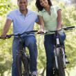 Couple on bikes outdoors smiling — Stock Photo