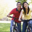 Couple on bikes outdoors smiling — Stock Photo #4767955