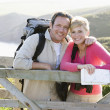 Couple on cliffside outdoors leaning on railing and smiling - Stock Photo