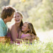 Family at park having a picnic and laughing — Stock Photo