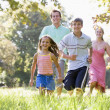 Family running outdoors smiling - Stok fotoğraf