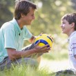 Man and young boy outdoors with soccer ball smiling — Stock Photo