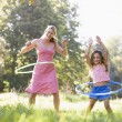 Woman and young girl with hula hoops outdoors smiling - Stock Photo