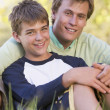 Man and young boy sitting outdoors smiling — Stock Photo