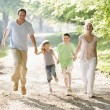 Family running outdoors holding hands and smiling - 图库照片