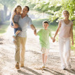 Family walking outdoors holding hands and smiling — Stock Photo