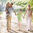 Foto Stock: Family walking outdoors holding hands and smiling