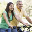 Man and girl on bikes outdoors smiling — Zdjęcie stockowe #4768009