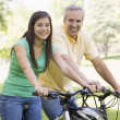 Foto Stock: Mand girl on bikes outdoors smiling