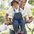 Foto Stock: Man and young boy on a bike outdoors smiling
