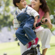Woman and young boy on a bike outdoors smiling — Stock Photo