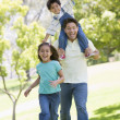 Man with two young children running outdoors smiling — Stock Photo