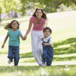 Woman with two young children running outdoors smiling — Stock Photo