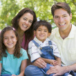 Family sitting outdoors smiling — Stock Photo #4768025