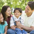 Family sitting outdoors smiling — Stock Photo