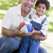 Man and young boy outdoors with football smiling — Stock Photo