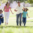 Family running outdoors smiling - 图库照片