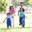 Family running outdoors holding hands and smiling - Stock fotografie