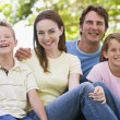 Family sitting outdoors smiling — Stock Photo #4768063