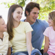 Family sitting outdoors smiling — Stock Photo #4768065
