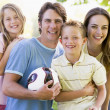 Family standing outdoors holding volleyball smiling — Stock Photo #4768079