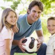 Man and two young children outdoors holding volleyball and smili — Stock Photo #4768081