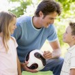 Man and two young children outdoors holding volleyball and smili — Stock Photo #4768082