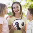 Woman and two young children outdoors holding volleyball and smi — Stock Photo #4768084