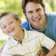 Foto Stock: Man and young boy outdoors embracing and smiling