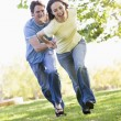Couple running outdoors holding hands and smiling — Stock Photo #4768087