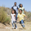 Family running on path smiling — Stock Photo