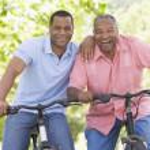 Two men on bikes outdoors smiling — Stock Photo