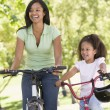 Woman and young girl on bikes outdoors smiling - 